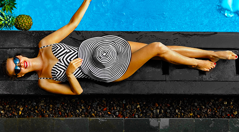 woman by pool in swimsuit with smooth skin