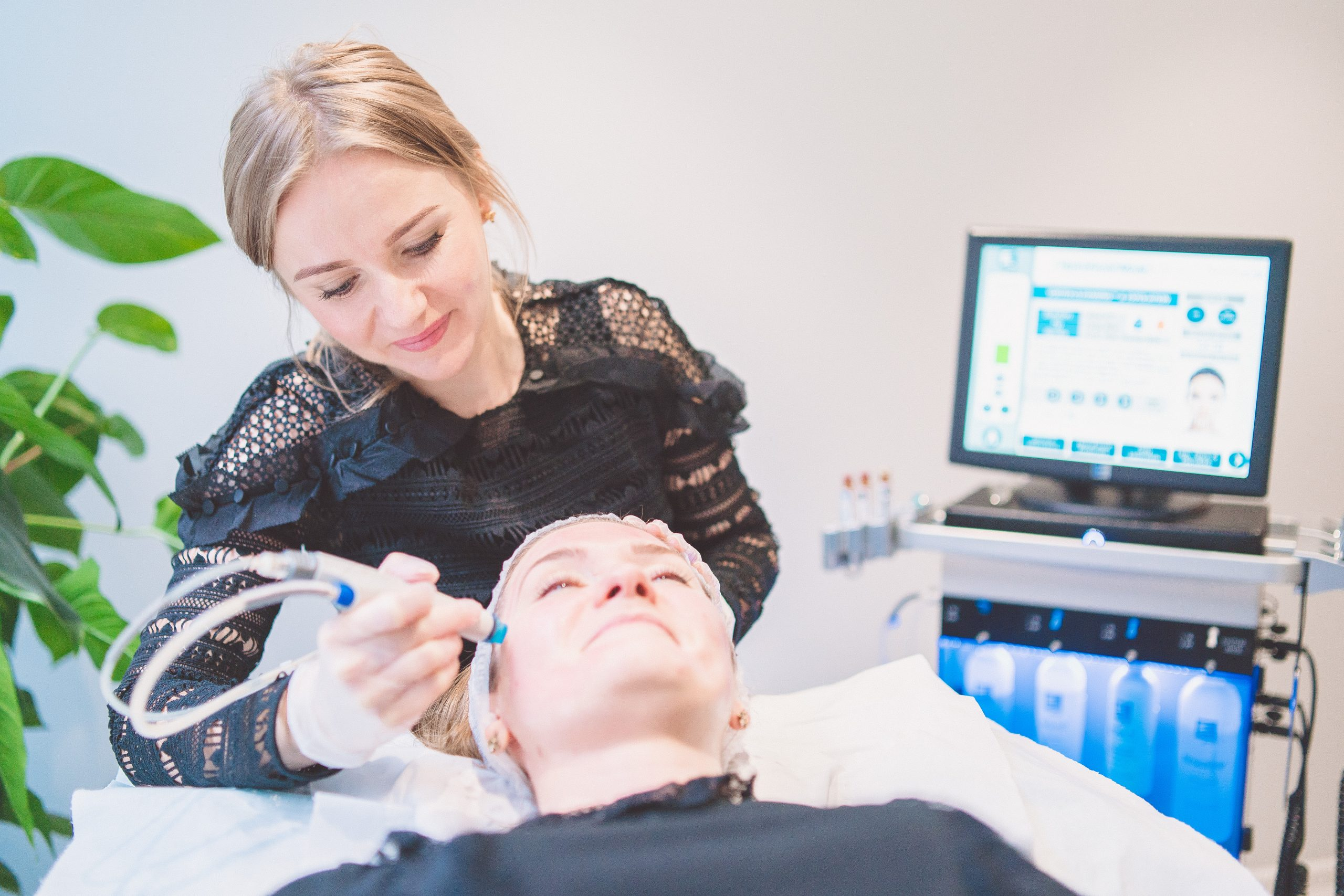 Female Practitioner performing HydraFacial on Woman